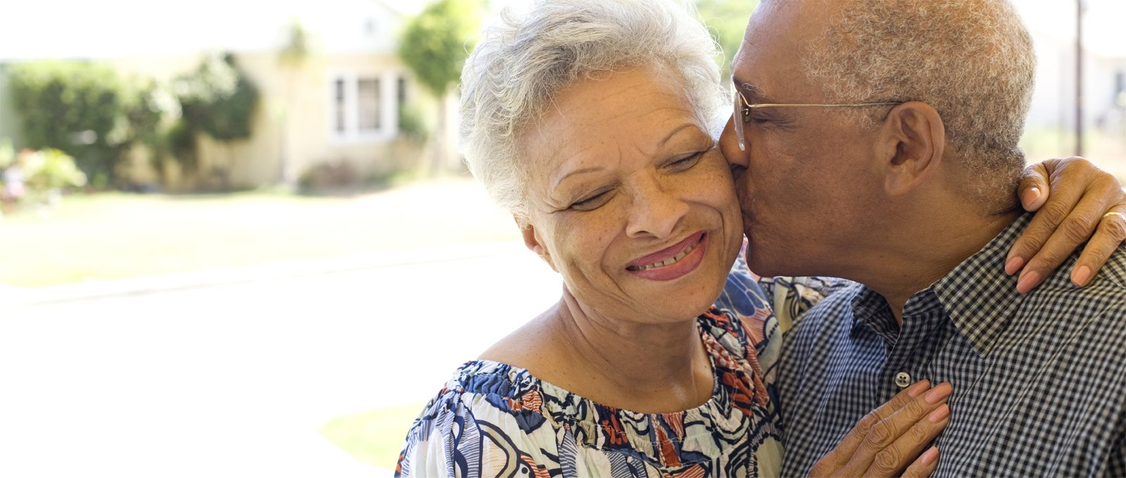 older couple embracing on front porch