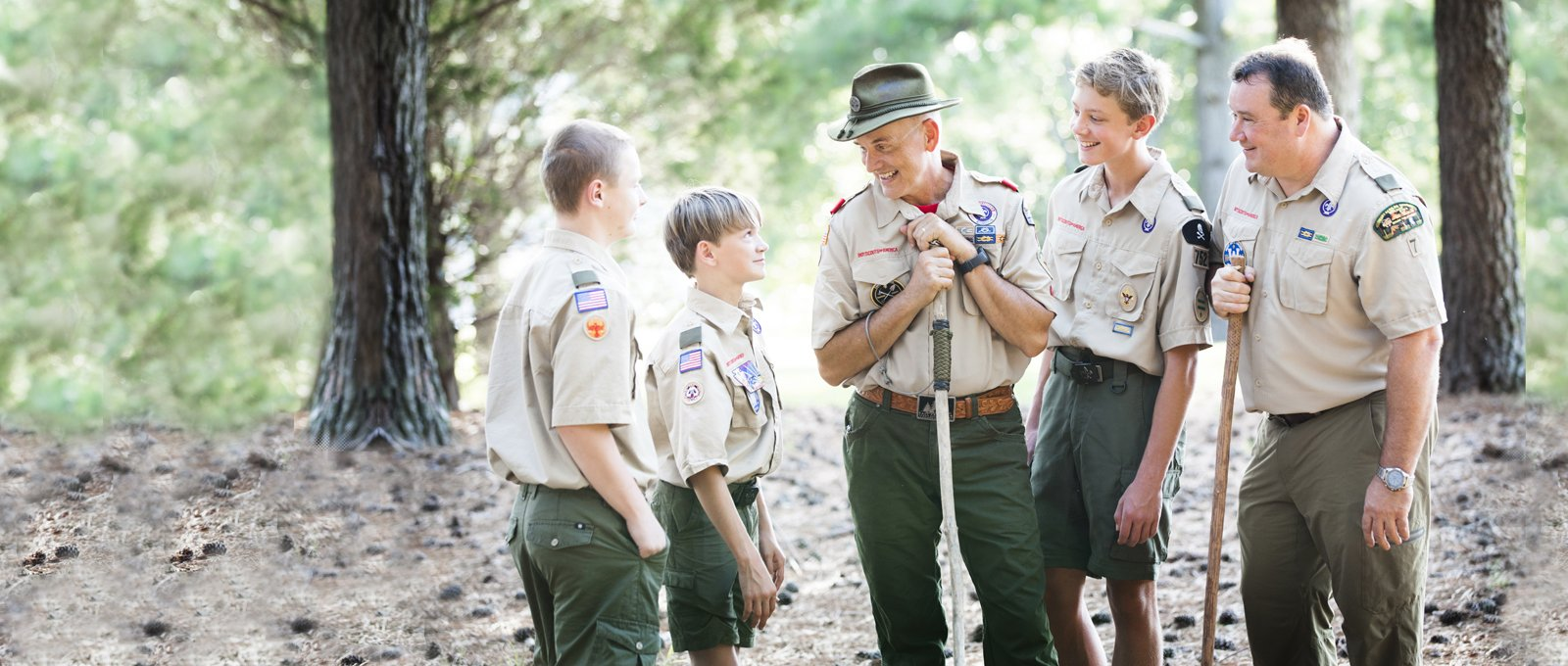 scout leaders talking to two scouts while on a hike